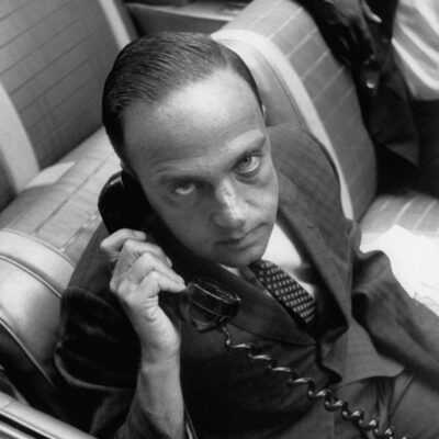 Lawyer Roy Cohn sitting in front seat of his 1961 Chevrolet Impala convertible